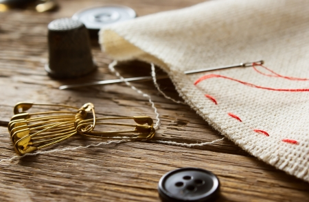 Needle and natural linen canvas texture for the on wooden table  Stock Photo - 23054492