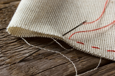 Needle and natural linen canvas texture for the background on wooden table  photo