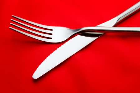 red tablecloth: Fork and knife on red tablecloth Stock Photo