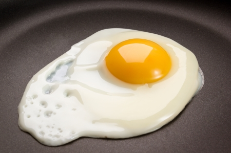 Fried egg on frying pan Stock Photo