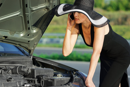 car trouble: Woman with telephone near the broken car