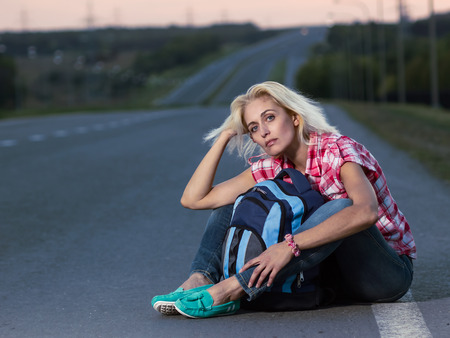 haversack: Hitch-hiking: woman with haversack sitting on the road Stock Photo