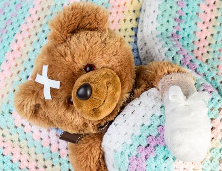 Sick teddy bear with bandage in a bed Reklamní fotografie