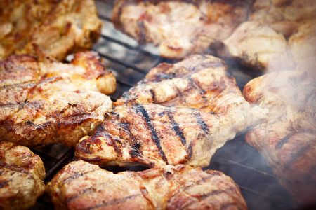 charbroiled: Meat on darbecue grill flames