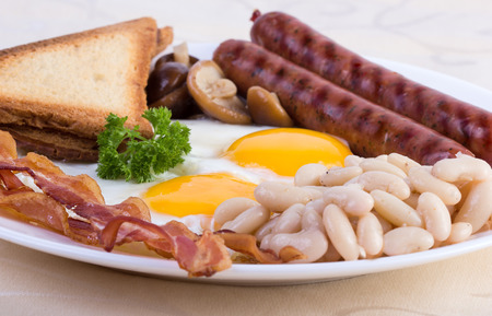 English breakfast: eggs, beans, sausages, bacon and mushrooms photo