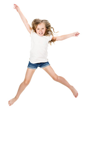 pre schooler: Little girl jumping over a white background