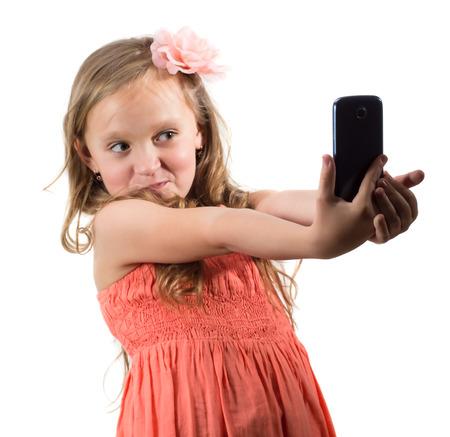 흰색 배경 위에 그녀의 자신의 사진을하는 어린 소녀