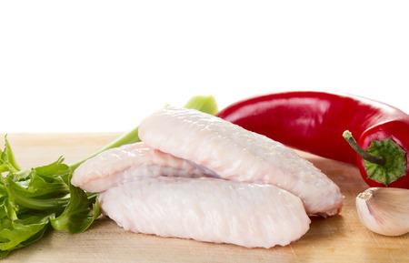 Alas de pollo crudo con ajo, pimienta y selery aislados sobre fondo blanco