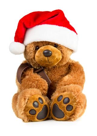 osos navideños: Juguete del oso de peluche que lleva un sombrero de santa aislado en el fondo blanco Foto de archivo