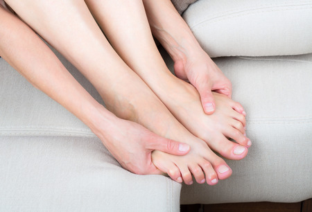 Woman sitting on sofa, close up view of legs and hands Stock Photo