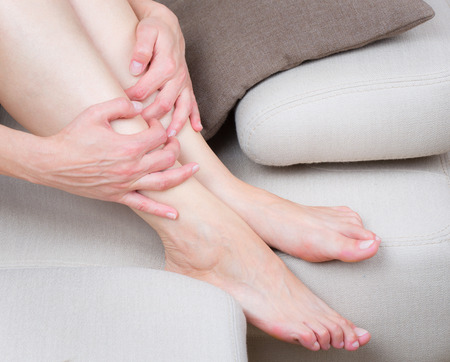 Close up view of tired woman legs on the sofa Stock Photo