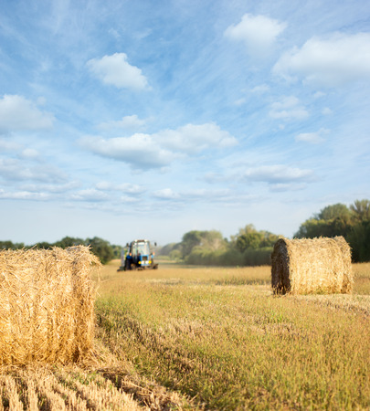 agronomics: Tractor throwing out hay roll