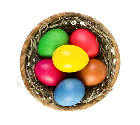 Easter eggs in nest basket isolated on white background. Top view photo