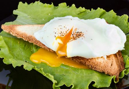 Tostadas con lechuga y huevo escalfado sobre una placa de negro para el desayuno. acercamiento Foto de archivo