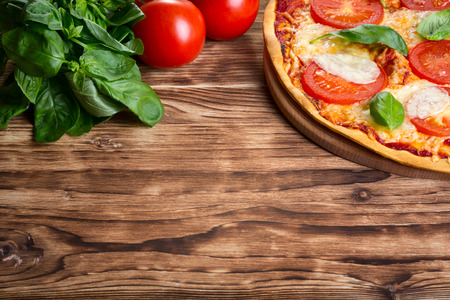 melted cheese: Close up view of pizza Margarita on wooden background Stock Photo