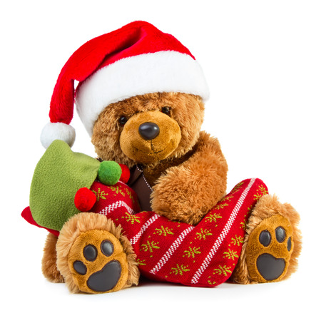 Teddy bear wearing a santa hat with christmas stocking isolated on white background