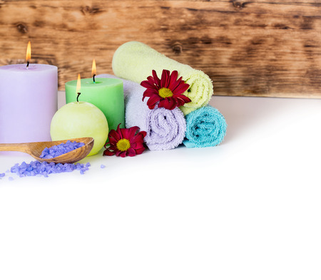 background settings: Spa massage background with rolled towel, candles, sea salt and fresh flowers Stock Photo