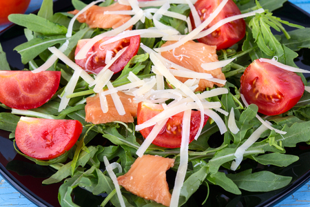 green vegetable: Salmon salad on black plate with green leaves and cherry tomatoes Stock Photo