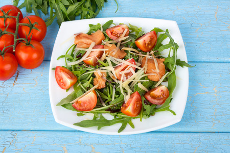 diet dinner: Salmon salad with aragula and cherry tomatoes on white plate on blue wooden background