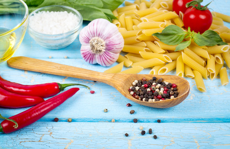 Pasta ingredients on blue wooden background