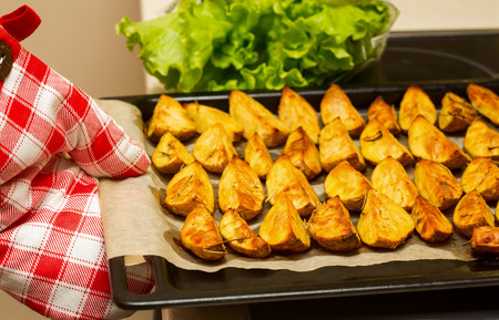 ovenbaked: Kitchen protective glove with ovenbaked potatoes with garlic and herbs