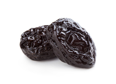 Close up view of two prunes isolated on white background