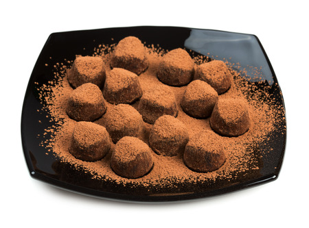 Chocolate truffles on black plate isolated on white background Фото со стока