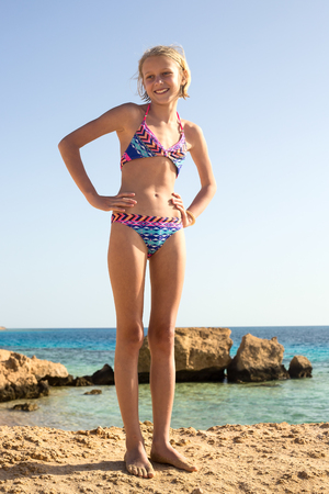 Beautiful shy child girl standing on the Red Sea beach Stock Photo