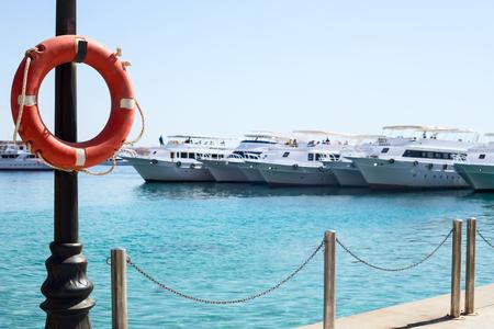 salvavidas: Lifebuoy en la playa con barcos en el muelle