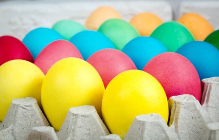 Painted multicolored Easter eggs in carton tray