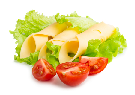 Cheese slices with cherry tomatoes on green salad leaves isolated on white background