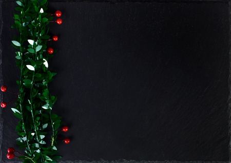 Christmas black background with holly berry