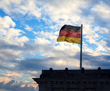 German flag on cloudy sky background in Berlin. Germany