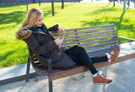 Young beautiful woman sitting on bench in green autumn square