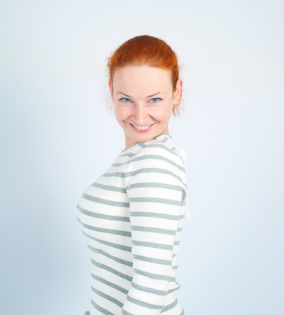 Pretty redhead smiling woman posing against light background Reklamní fotografie