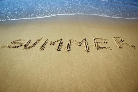 Inscription of Summer on sand sunny beach with blue waves
