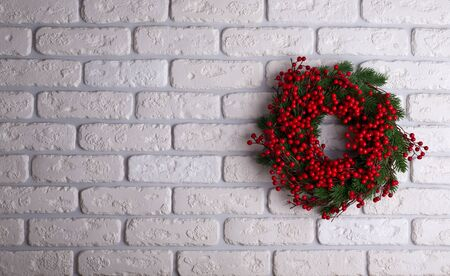 Christmas wreath on brick wall background. Holiday concept