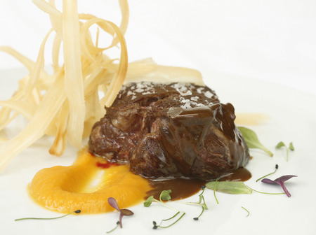 roast beef tenderloin with sweet potato cream and fried yucca Imagens