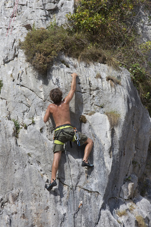 steep cliff: young man climbing a steep cliff Stock Photo