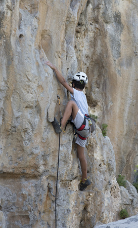steep cliff: child with helmet climbing a steep cliff Stock Photo
