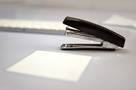 black stapler on a white table, near a white sheet of paper, office stationery