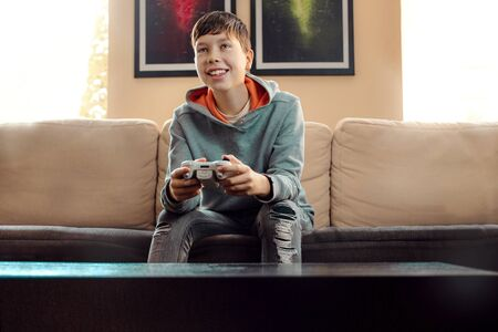 a cheerful boy sits on a sofa at home and plays on a game console, happy to win