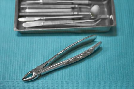dental forceps for wisdom tooth extraction, dental extraction forceps, on a blue background, in the background a tray with dental instruments