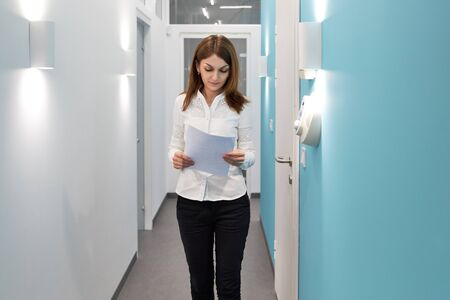 business woman working at the reception in the hospital, girl with documents at the reception in the office, administration