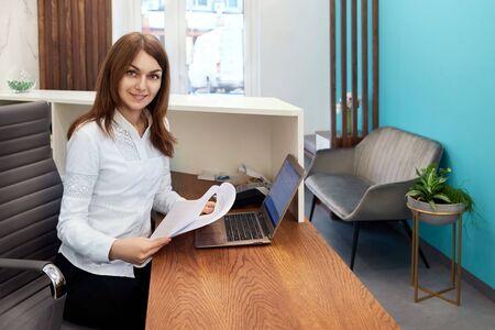 Femme heureuse souriante travaillant à la réception dans un hôpital, fille à la réception au bureau, administration