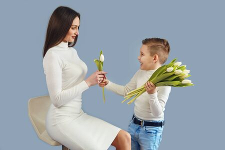 Happy mothers day6 The son the child congratulates mother and gives her flowers of tulips. Mom and son are smiling and hugging. Family holidays and communication. spring, holiday greetings