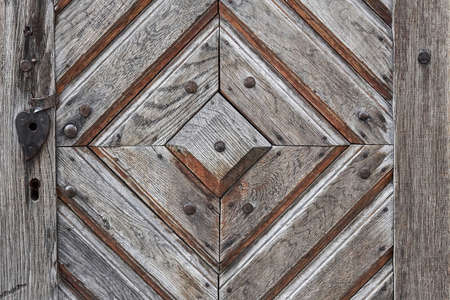 detail of a wooden barn door with wood plank patterns and an iron heart shaped key hole
