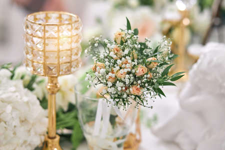 On the table is a delicate floral arrangement of roses in a glass vase and a candlestick. Wedding decorations. Imagens