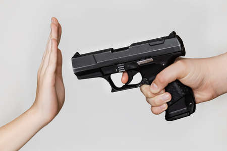 I want to shoot a pistol in my hand, the other hand shows protest, do not shoot, against a light background.