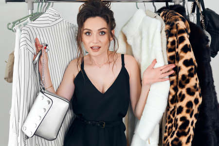 An attractive woman standing near hangers with clothes, with horror thinks what to wear at a business meeting with her comrades. Fashion woman having many clothes